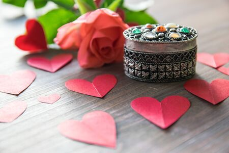 Vintage beautiful silver casket with stone, pink flower, red paper hearts. Vintage composition for Valentines Day or Womens Day.
