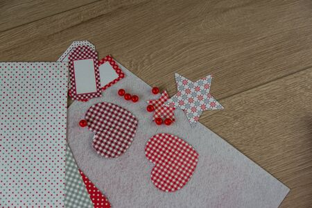 The red heart made of paper, handwork, and other materials for creation of a congratulation by Valentines Day or Mothers day on the wood table. Cold background. Hobby for children concept.