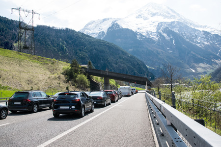 A lot of cars stay in traffic jam on the road near tunnel with mountains and forest in Switzerland.