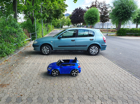 Two cars stay near on the parking place in summer day and trees around. Blue car for child and green car for adult standing side by side.