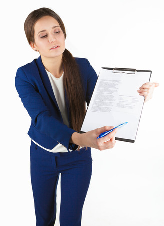 business costume: Young beautiful business woman in blue costume holds a document and points something out in it with her pen. Stock Photo