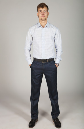 confidently: Young business man in white shirt stands confidently and boldly with hands in pockets Stock Photo