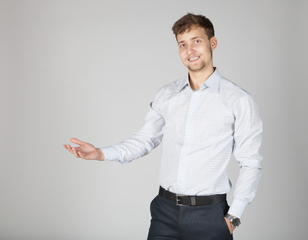 gesticulating: Young business man in white shirt present some information with joy and cheer gesticulating his hand.