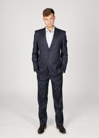 independently: Young business man in dark grey suit stands independently and confidently. Stock Photo