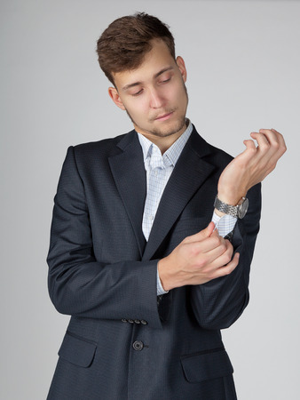 suit  cuff: Young business man in dark grey suit straightens his cuff. Stock Photo
