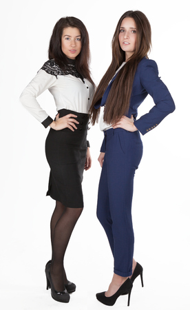 manager team: two beautiful young slim business women stand closely to each other and smile isolated.