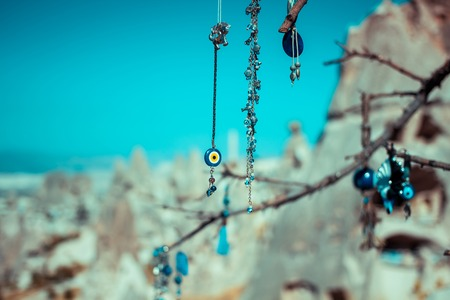 Evil eye charms hang from a bare tree in Cappadocia  photo