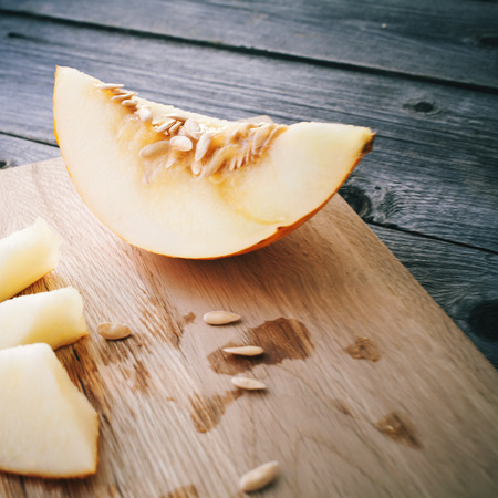 musk: Slices of honeydew melon on gray wooden table.