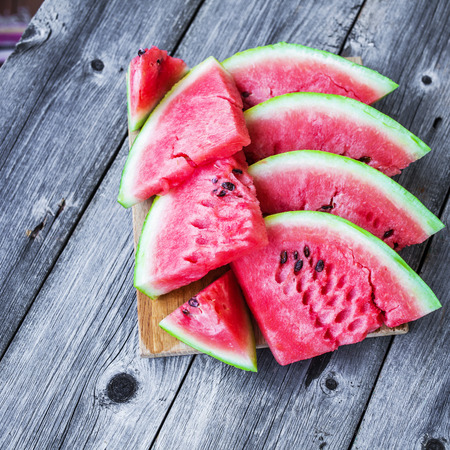 slices of watermelon  on a plate on a wooden background.