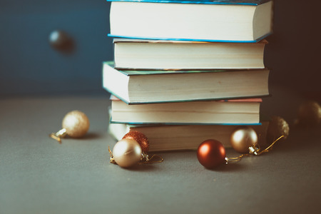 book background: Christmas decoration and books on gray table.