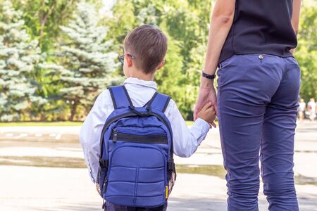 El niño es un alumno de primer grado con gafas y un maletín azul con la mano de su madre.