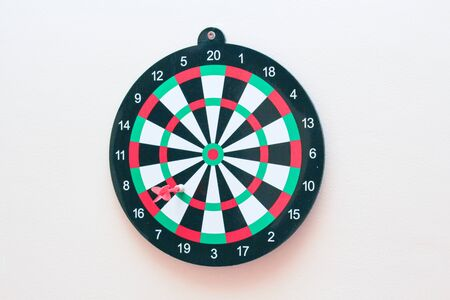 Dartboard with a dart on a gray wall close up. Darts game