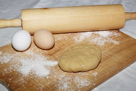 Womans hands roll out the dough with a wooden rolling pin on a wooden board