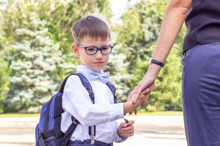 The boy is a first-grader in glasses with a blue briefcase holding his mother hand