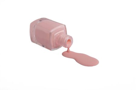 Pink nail polish is poured from the bottle on the table on a white background. Nail design. Beauty industry