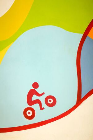 Sketchy picture on the wall of a red bicyclist riding up the hill on a colored background Banco de Imagens