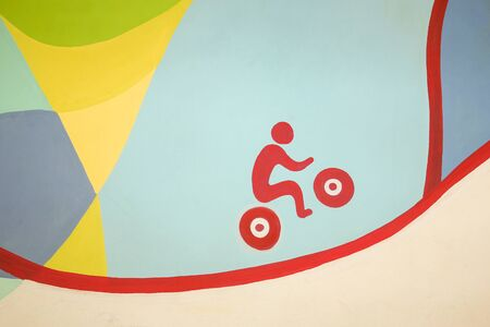 Sketchy picture on the wall of a red bicyclist riding up the hill on a colored background.  Drawing on the wall