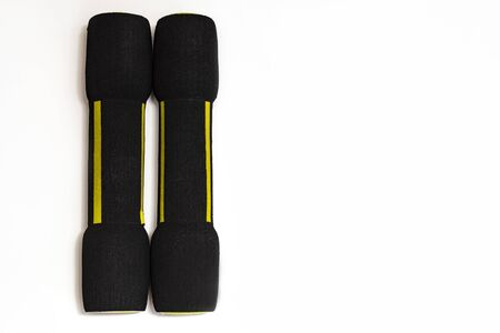 Two black dumbbells with a soft coating on a white background