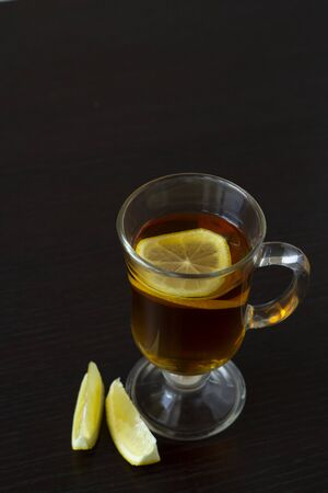 Tea with lemon in a glass cup on a dark background. View from above