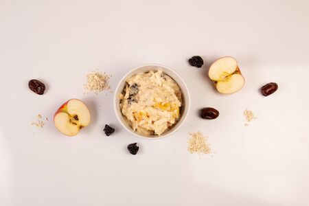 Salad of apple, orange, oat hops and prunes with honey in a white plate on a white background.
