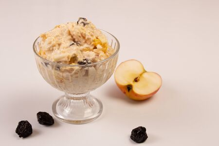 Salad of apple, orange, oat hops and prunes with honey in a glass plate on a white background. Vegetarian diet, view from above. Nearby lies a half apple and three prunes  Banco de Imagens