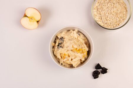 Salad of apple, orange, oat hops and prunes with honey in a white plate on a white background. Vegetarian diet, view from above. Nearby lies a half apple, two prunes and a bowl of oatmeal