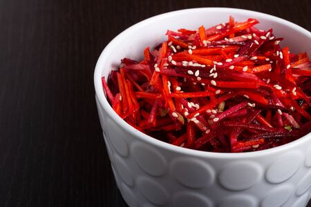 Vegetable salad of apple, carrot and beetroot with lemon juice, sesame seeds and vegetable oil in a white deep plate on a black background. Proper nutrition, raw food diet, vegetarianism