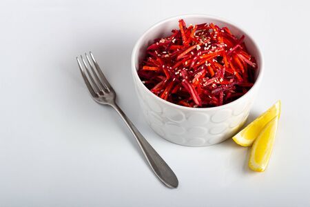Vegetable salad of apple, carrot and beetroot with lemon juice, sesame seeds and vegetable oil in a white deep plate on a white background. Proper nutrition, raw food diet, vegetarianism