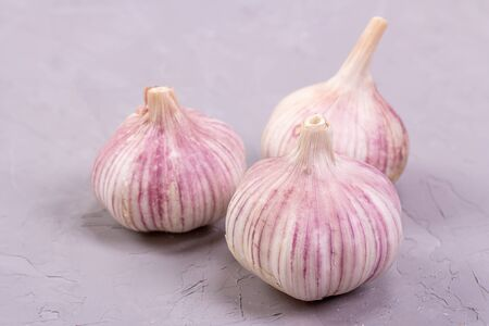 Three heads of garlic close-up on a gray background. Fresh garlic is good for health Reklamní fotografie - 147655425