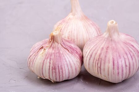 Three heads of garlic close-up on a gray background. Fresh garlic is good for health Reklamní fotografie - 147766284