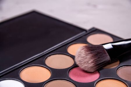 Makeup brushes, open can with blush palette of eyeshadows on a gray background, top view