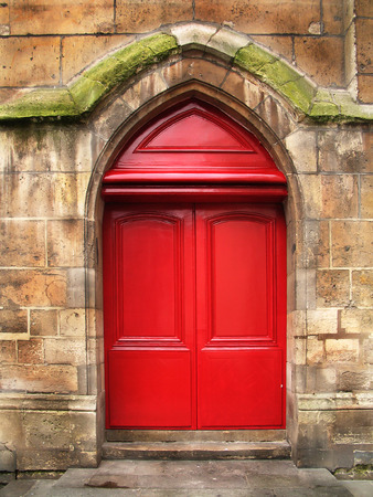 Red wooden doors, renovated, of the old stone cathedral.