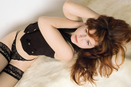 Red haired girl laying on the white fur carpet wearing delicate lingery and waistcoat photo