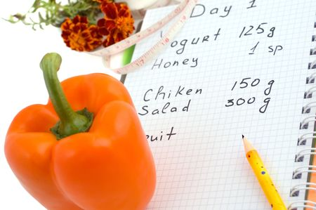 Diet-book, pepper and measure tape on white background