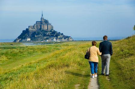 Senior couple walking towards Mont St. Michel, France