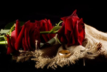 bagging: Wedding ring and roses on bagging. Isolated on black. Glamour styled.