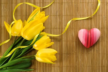 Yellow tulips and pink heart on a bamboo mat  Stock Photo - 2527651