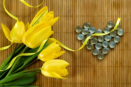 Yellow tulips and glass heart on a bamboo mat. Processed in painting-like style. Stock Photo - 2527649