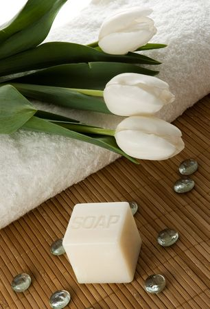 White towels, tulips and soap in a SPA composition.