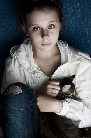 Teenage girl holding little cat against dark blue wall