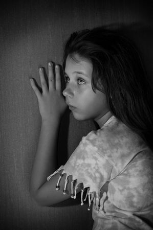 Teenage girl leaning against dark wall black and white photo