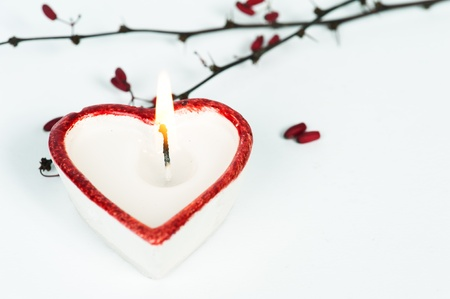 White and red heart-shaped candle with barberry tinted blue photo