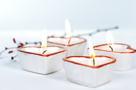 Four white and red heart-shaped candles tinted blue photo