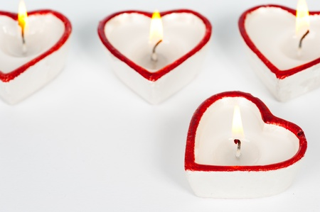 Four white and red heart-shaped candles  photo