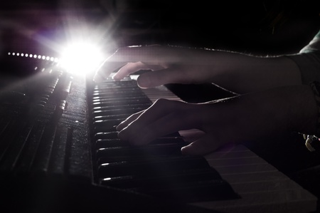 backlit keyboard: Hands above the piano keyboard in backlight