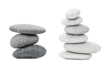 Two piles of black and white sea stones on white background