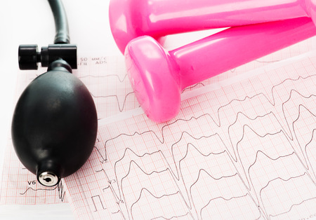 Sphygmomanometer and pink dumbbells lying on ECG diagram photo