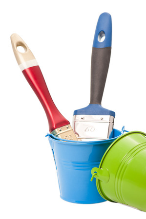 Paint brushes in green and blue tin buckets isolated on white photo