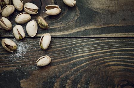 Closeup of pistachios nuts and salt on dark brown wooden table Banco de Imagens
