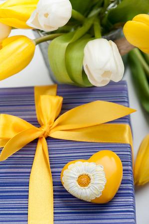 yellow heart: Purple gift box with yellow heart and ribbon, tulips Stock Photo